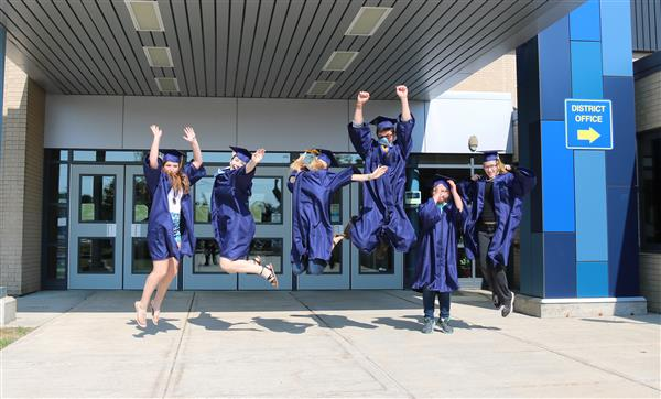 graduates jumping in front of the school