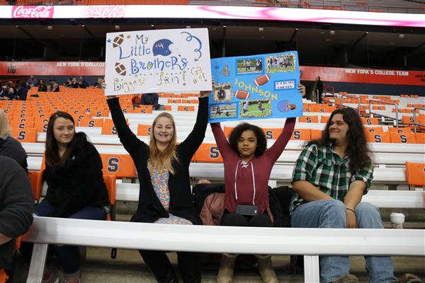 fans at dome game with signs