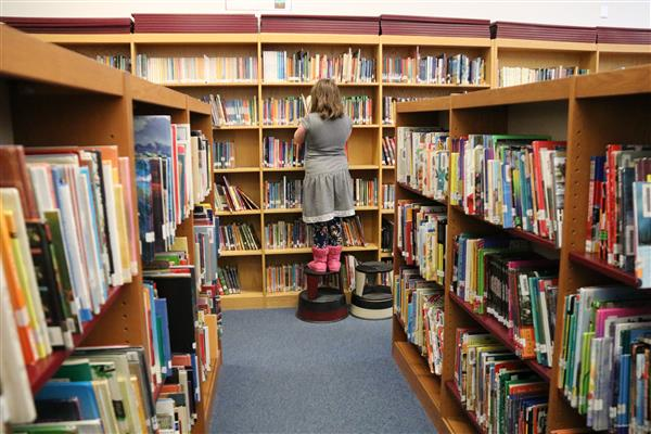 library shelves with student searching books