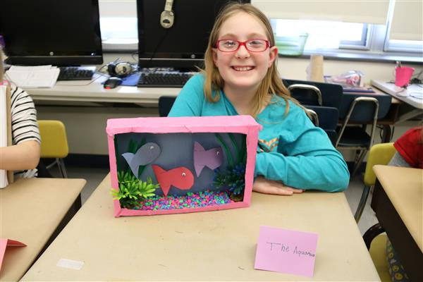 smiling student with aquarium project