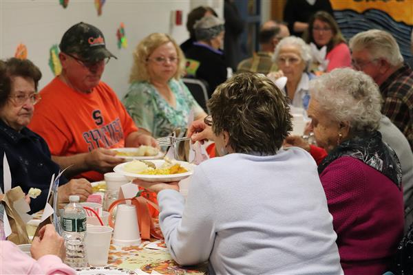 A table of seniors sharing food during the 33rd Annual Senior Citizen Thanksgiving Dinner.