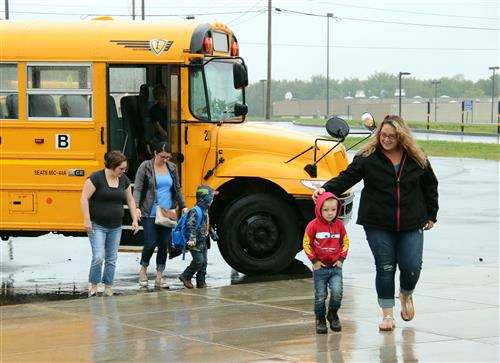 Parents and students heading into school after first bus ride.